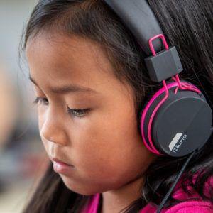 Meisje met kurio roze kinderhoofdtelefoon